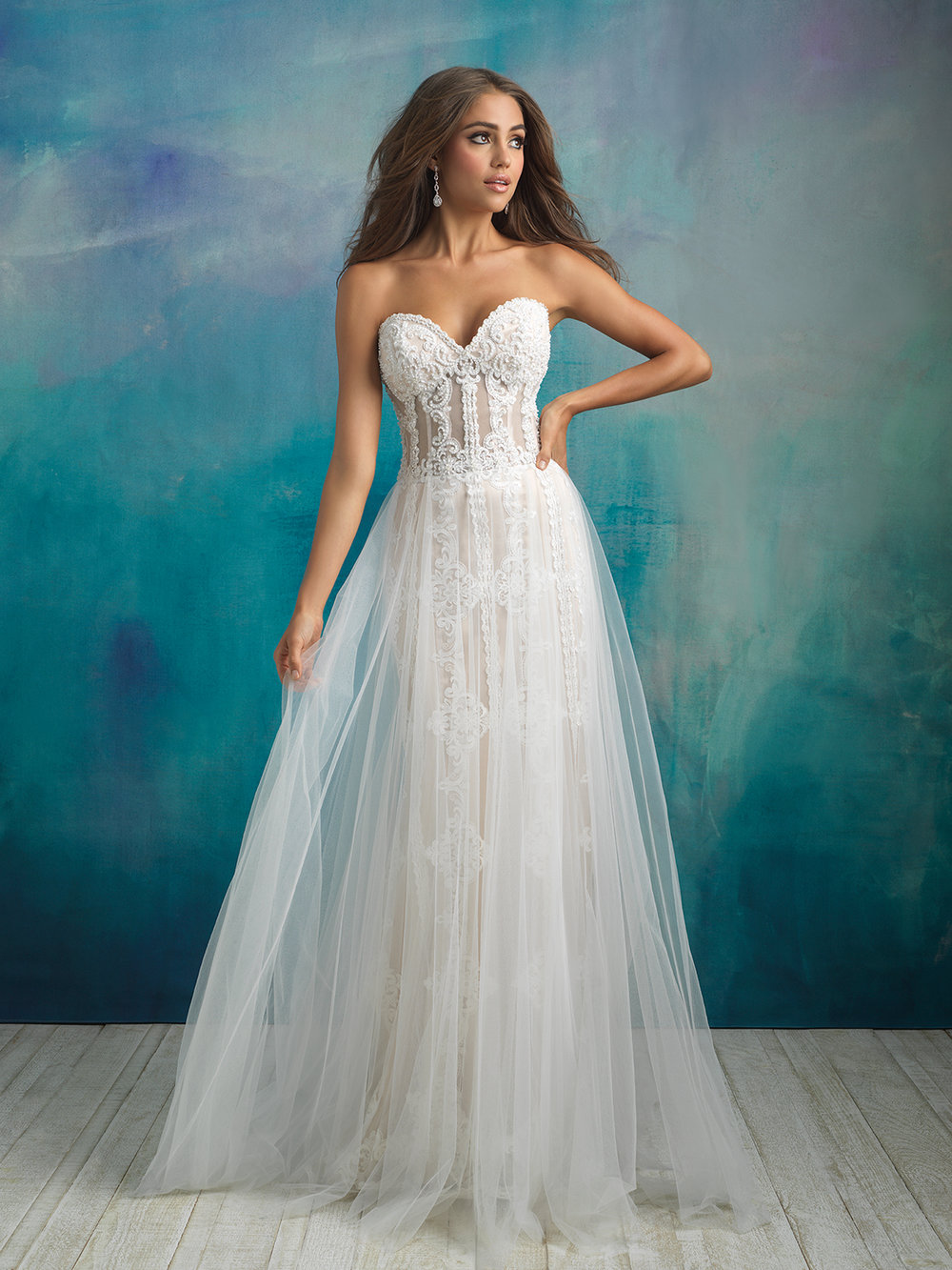Style 9523 - Elaborate beadwork, appliques and exposed boning is veiled by this gown's tulle overskirt.
