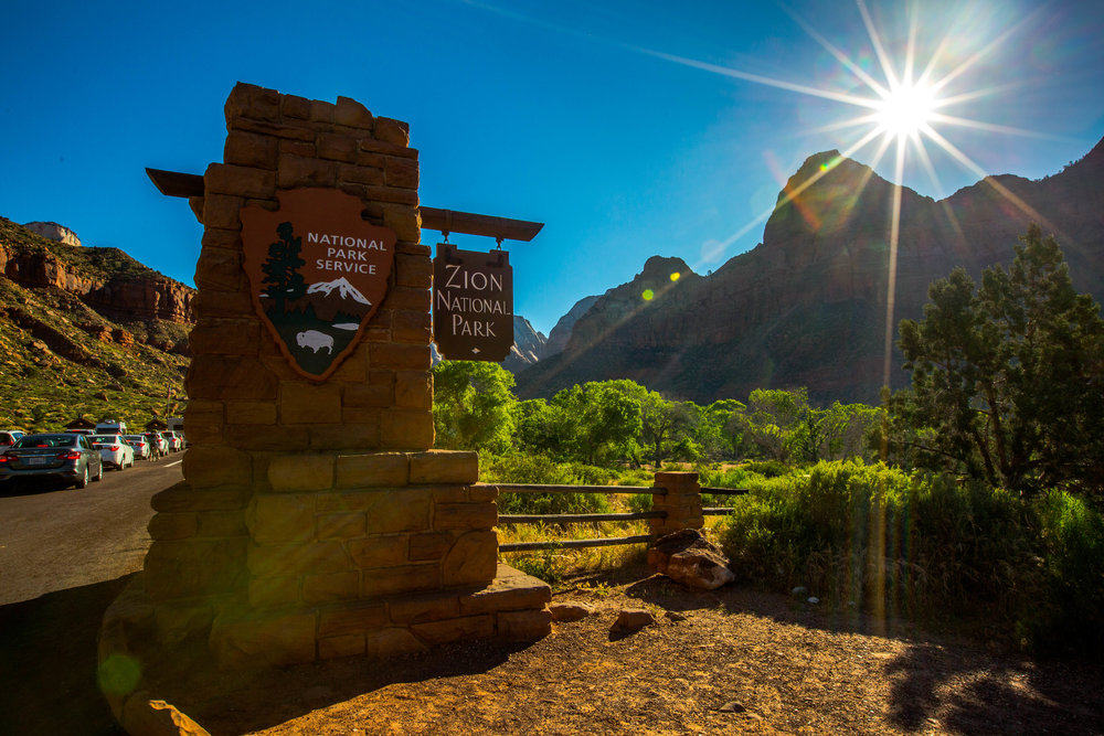 The entrance sign at Zion National Park (feat. a line of cars waiting to get in)