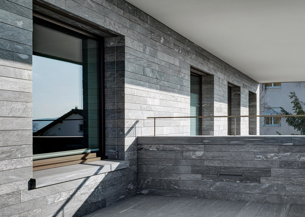 Balkon Haus am Hang - Bei der Fassade aus Naturstein wurde das mechanische Befestigungssystem StoneFix eingesetzt.