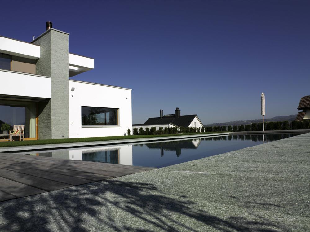 Im Aussenbereich sind sowohl die Bodenplatten als auch ein Zierstück der Fassade in Stein gestaltet.