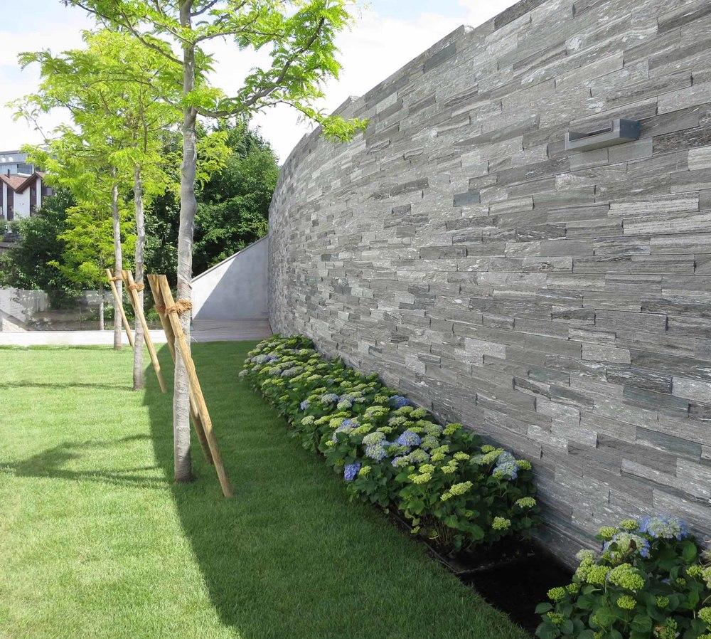 Die Gartenmauer aus Naturstein verleiht dem Grundstück Eleganz.