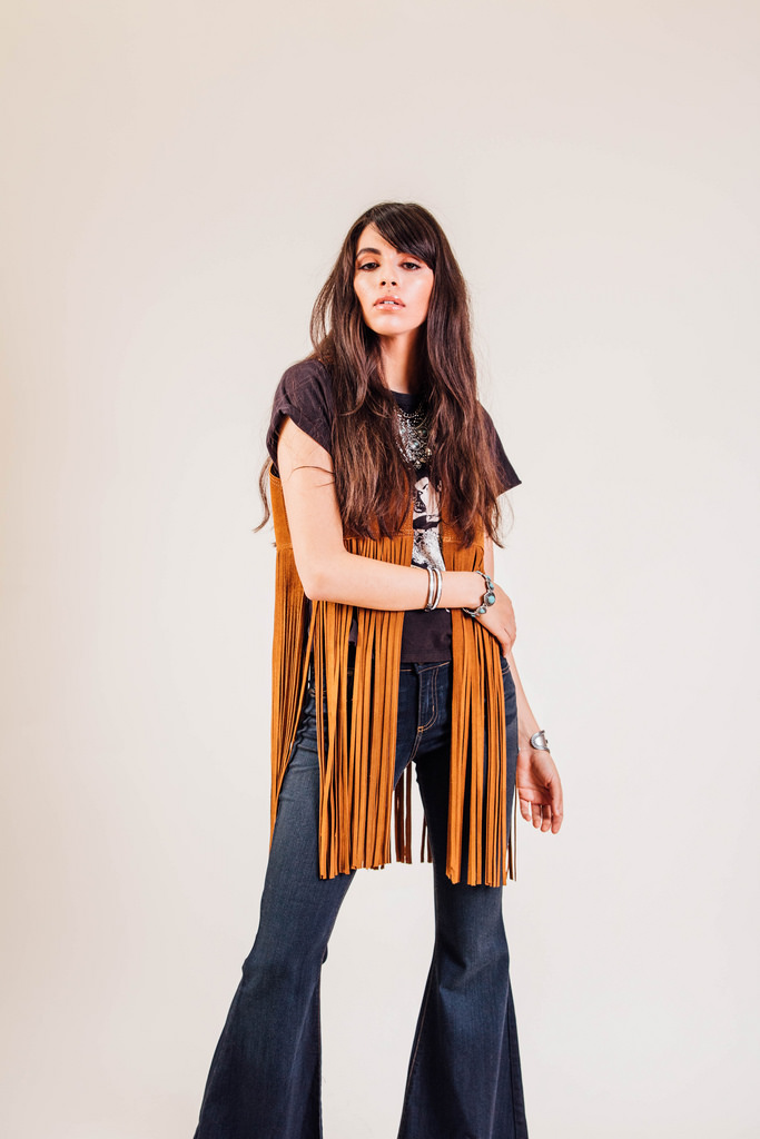 Madonna Boxy Tee  by Nasty Gal. Ella Denim Super Flares by Free People.  Wild West Suede Fringe Vest  by Free People.  Turquoise and Chain Bib Necklace  by Express.  Southwestern Teardrop Stretch Bracelet  by Express.  Double Wrap Rhinestone Bracelet  by Express.  Black Oval Cuff Bracelet  by Express.