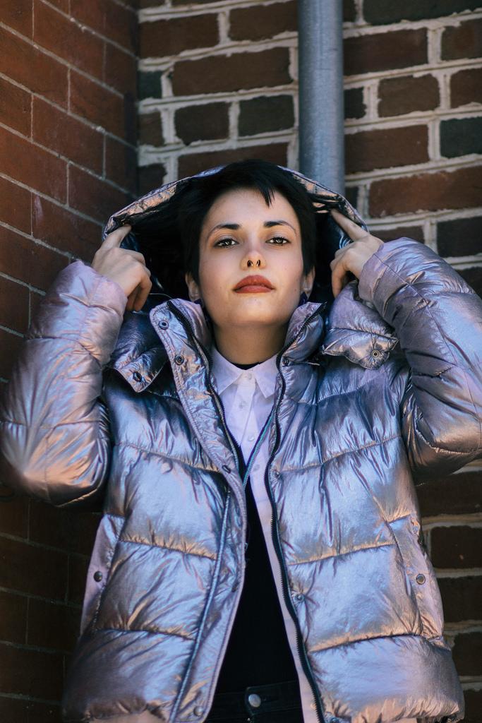 Model: Maider de Emilio Diaz. Silver ski jacket: Zara. White sleeveless blouse: Zara. Necklace and jeans: mode's own. Burgundy boots: Doc Marten, model's own.