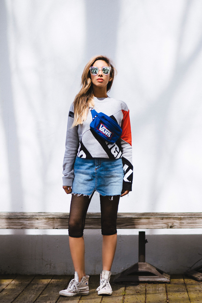 Cropped Sweatshirt with Mesh Sleeves: Adidas Originals. Fishnet cropped leggings: Boohoo. Electric Blue Old School Belt Bag: Vans. Denim Miniskirt: BDG. White canvas hightops: Converse. Sunnies: Quay Australia.