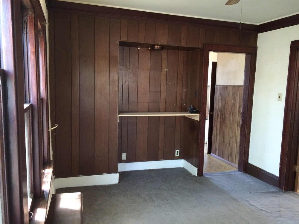 south wall. door to kitchen way. strange wood paneling built in.