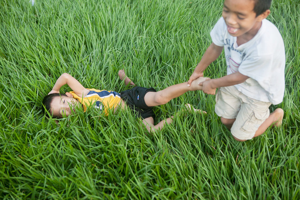 Jafet and Brayan playing in the tall grass.