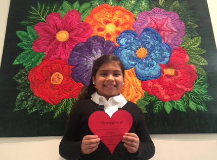 A young artist participates in #HeartsforArt in front of Love in the Language of Flowers by Lin Schiffner, fabric art