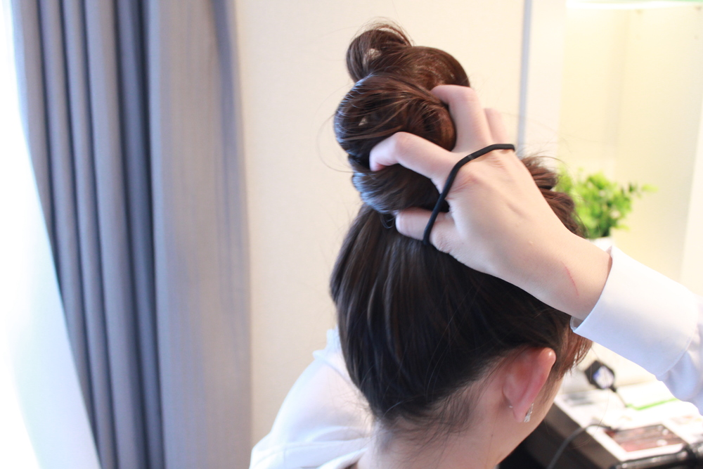 Adjust and twist until it forms a proper bun.  Tie it with another rubberband to hold it tight.