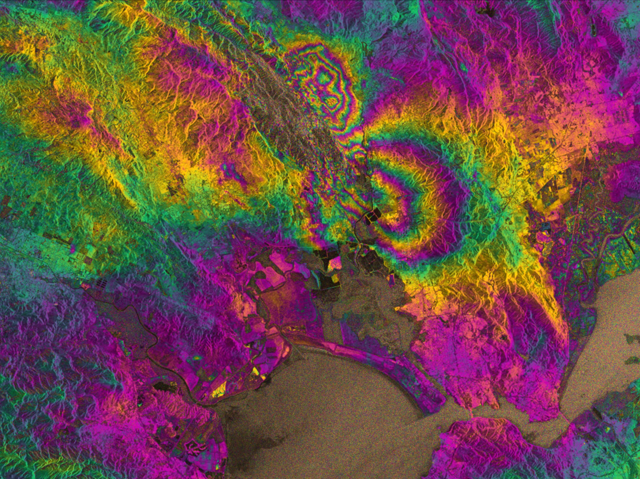 scienceisbeauty: Napa Valley quake. The biggest earthquake in 25 years struck California's Napa Valley in the early hours of 24 August 2014. By processing two Sentinel-1A images, which were acquired on 7 August and 31 August 2014 over this wine-producing region, an interferogram was generated. The two round shapes around Napa valley, which are visible in the central part of the image show how the ground moved during the quake. Deformation on the ground causes phase changes in radar signals that appear as the rainbow-coloured patterns. Each colour cycle corresponds to a deformation of 28 mm deformation. The maximum deformation is more than 10 cm, and an area of about 30x30 km was affected significantly. (Via esa)