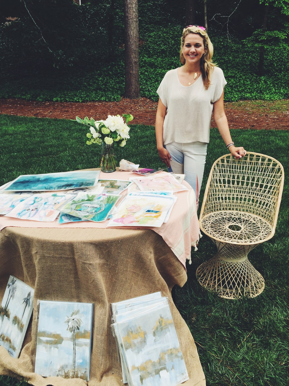 Maggie Mathews standing with her beautiful works and the best chair at the show.