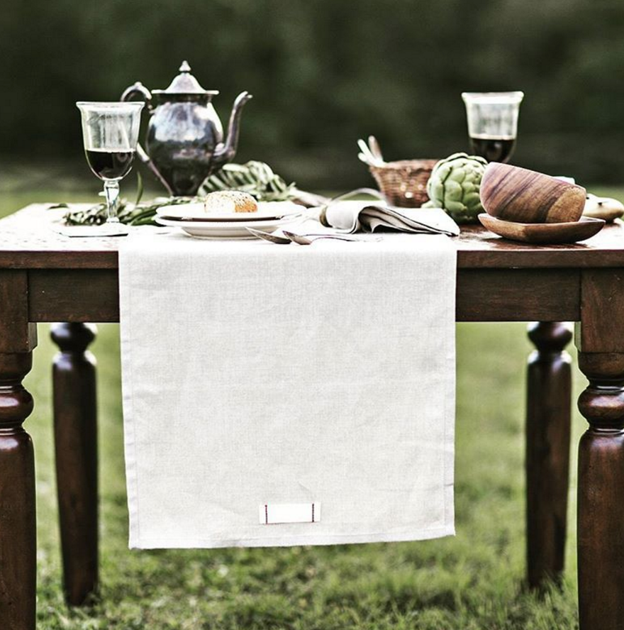 Photograph of a beautiful outdoor dining spread, featuring products from  Heirloomed Collection.