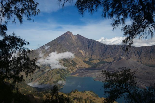 Gunung (Mount) Rinjani is an active 3726m (12,224ft) volcano on the island of Lombok, Indonesia. Towards the top of the volcano is a large, lake-filled lake known as Segara Anak or Anak Laut (Child of the Sea.) The lake is estimated to be about 200m (660ft) deep. A few days after I took in this tranquil scene the smaller volcano in the caldera, Gunung Barujari erupted and ejected ash many kilometres into the sky, forcing an emergency evacuation of the area.  Follow @tribaleye for updates, outtakes, unpublished and archive material  #landscape #indonesia #gunungrinjani #mountrinjani #rinjani #lombok #volcano #hiking #southeastasia #nusatengarra #caldera #activevolcano #journalism #photojournalism  #documentaryphotography #reportage #seetheworld #igtravel #hot_shotz #lensculture #visualarchitects #photooftheday #globalnomads @tribaleye