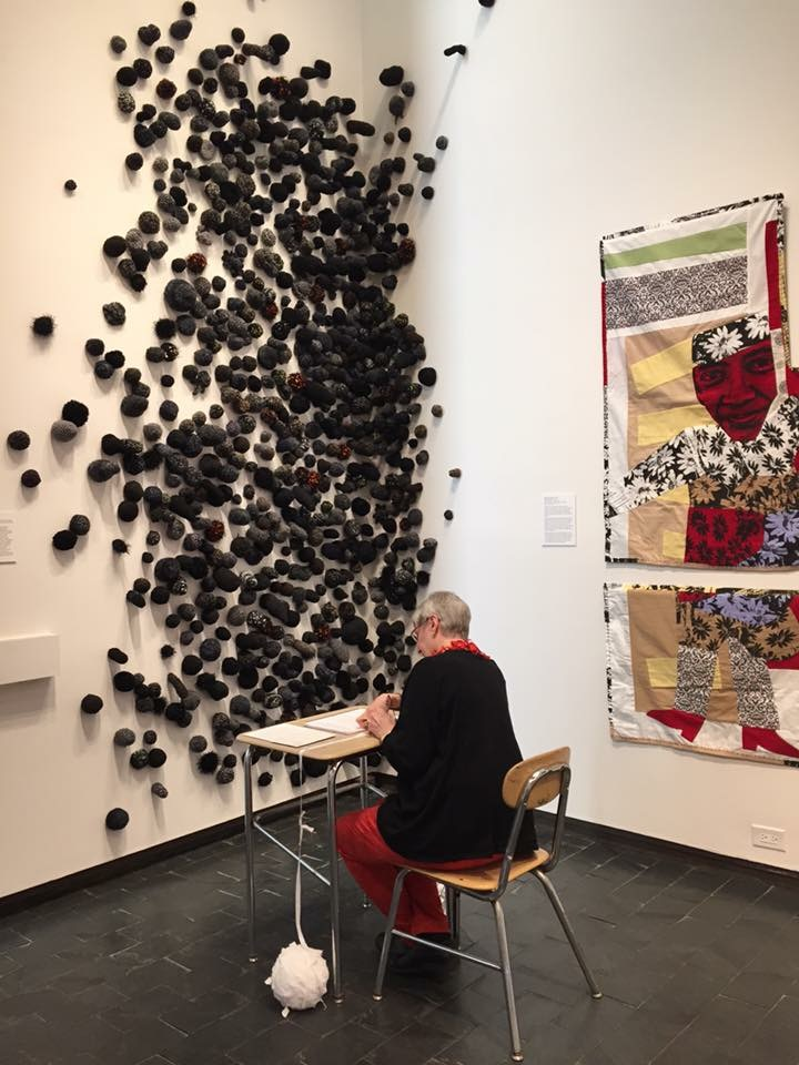 Creep    is the wall mounted installation in front of the seated woman. Each individual crocheted soft sculpture represents a child killed by a gun in 2015. A total of 823 children are represented on the wall.