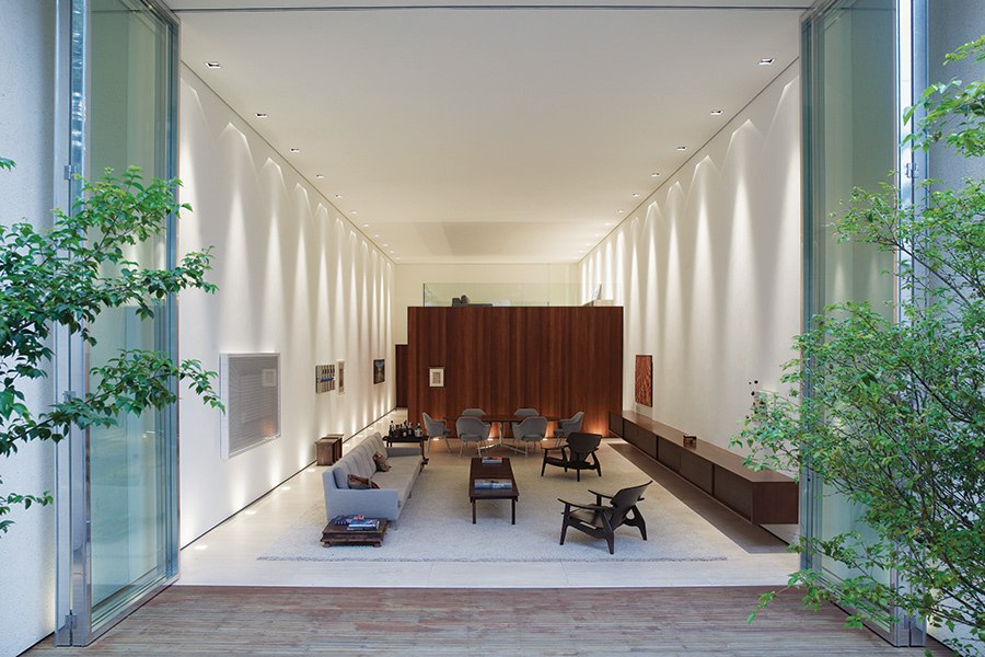 Designed by architect Marcio Kogan's firm, Studio MK27, Casa Corten in central São Paulo features a high-ceilinged ground-floor living space with retractable glass doors that open onto the back garden.