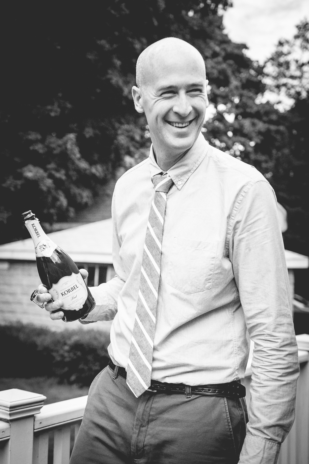 Groom popping the champagne backyard wedding celebration photographer Northshore MA