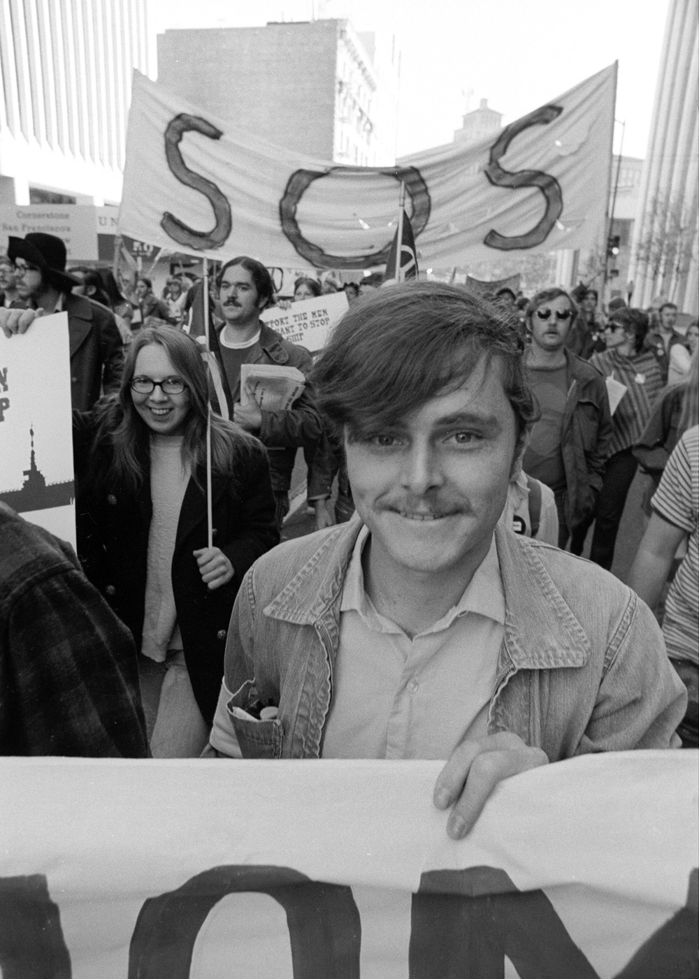 This sailor is happy to be marching with the Stop Our Ship group from the USS Coral Sea. This contingent led this anti-war march down Market Street on November 6,  1971.