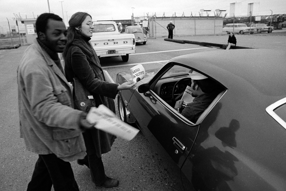 Two civilian supporters of the SOS campaign leaflet sailors as they drive to work at NAS Alameda