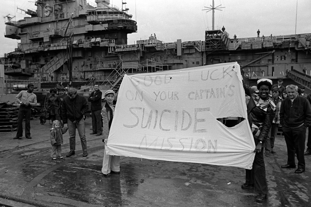 Rose Hills (right) and Vicky Kelly (right) unfurl their banner to the crewman on board the USS Coral Sea as they prepare to ship out on December 5, 1974.