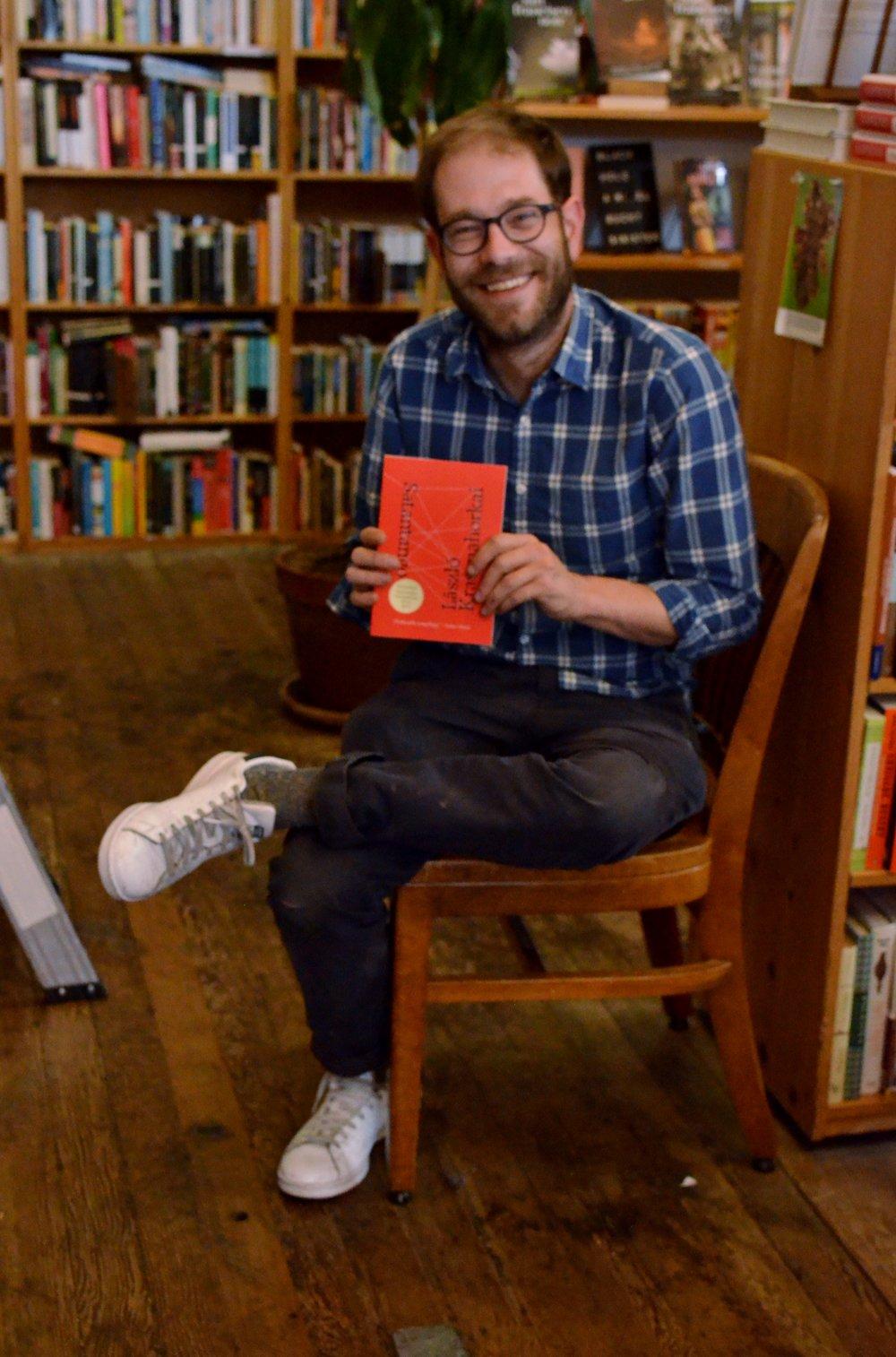 Ryan Smith of Valencia Dog Eared Books holding a current favorite novel, Satantango by Laszlo Krasznahorkai.