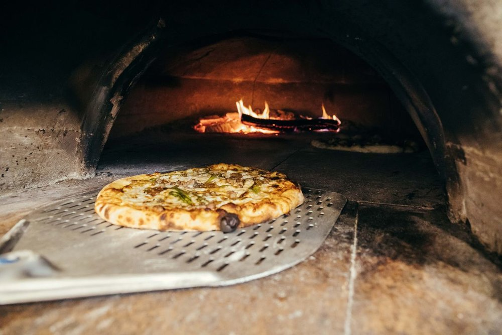 Our Meatball Pizza coming out of the wood-fired oven.