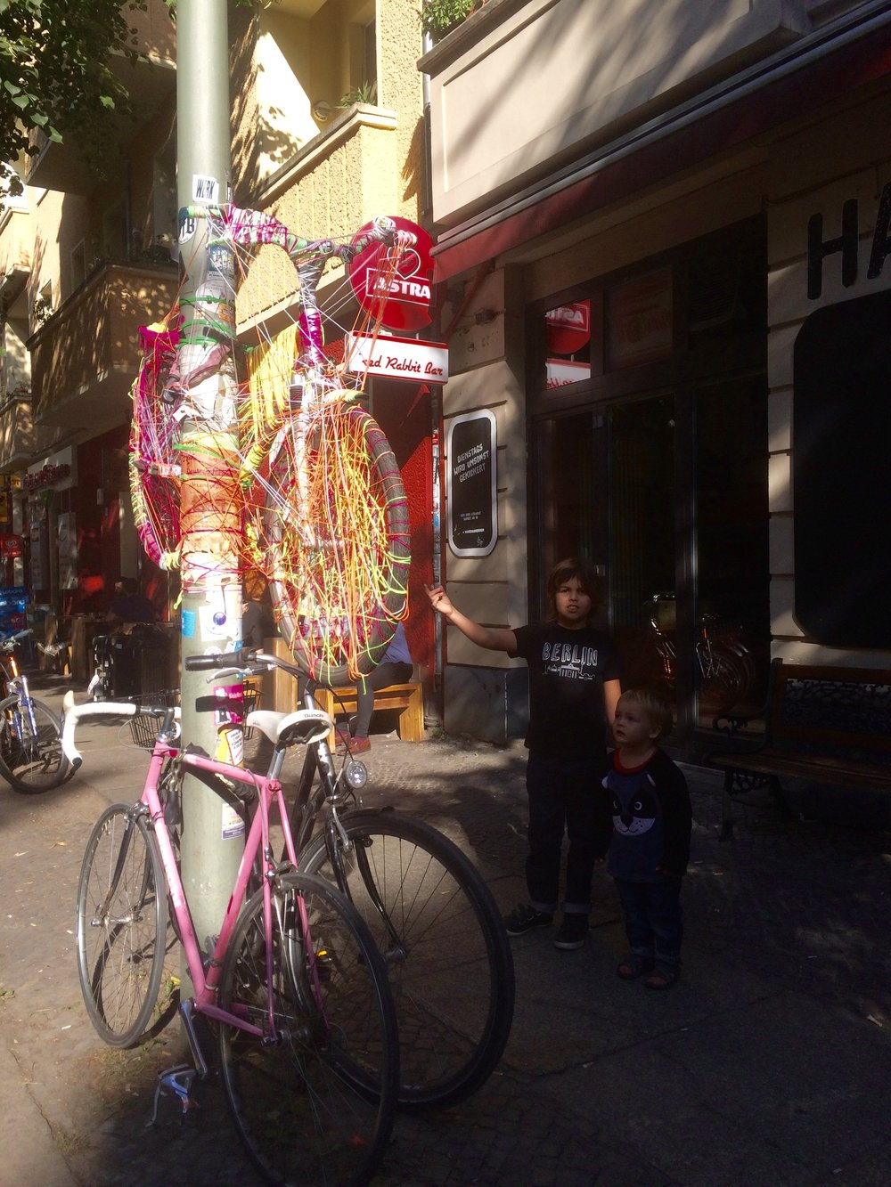 When we went to this shop, to send off a letter I wrote to my class. We posted the letter. When we got out we founds this bicycle hanging up. It was knitted onto the light pole. It looks really colourful and cool.