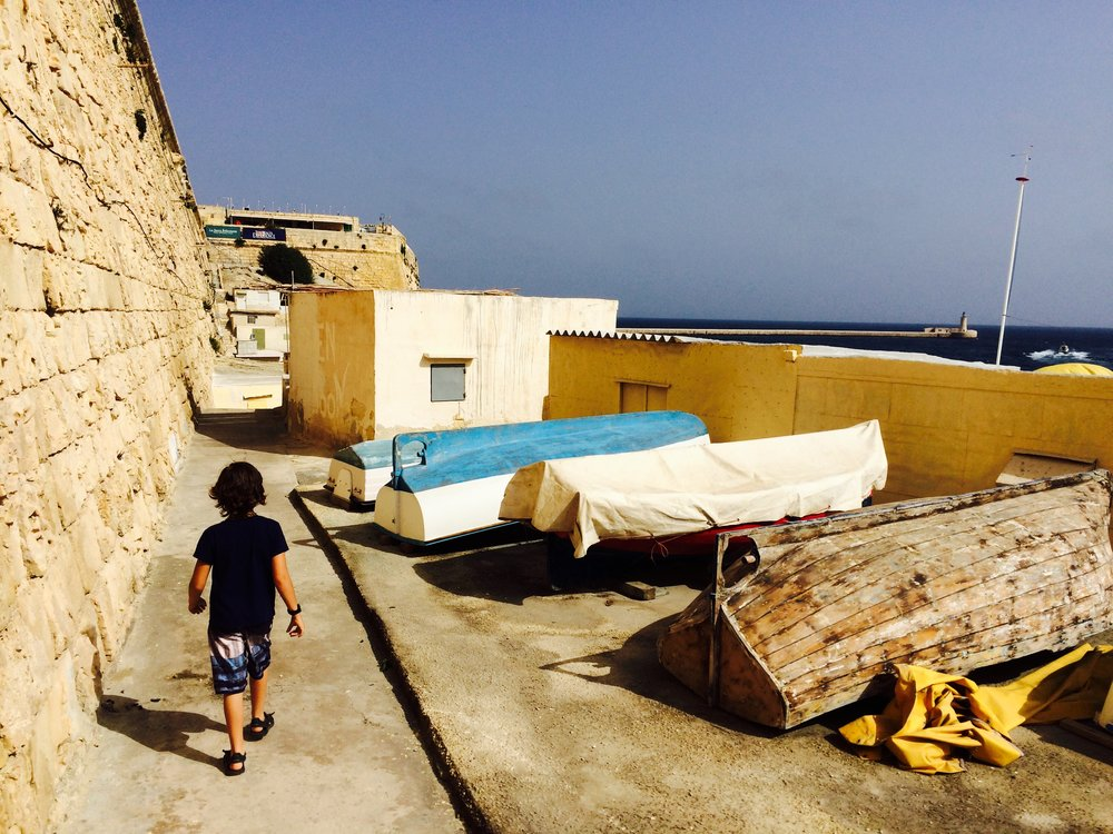 we found a beach to swim on and the waves were really strong but fun. Valetta has big fort walls which were to keep out the pirates. They would shoot cannons at the pirates if they came close. Sometimes the wall would break. This is a small fishing huts below the walls.