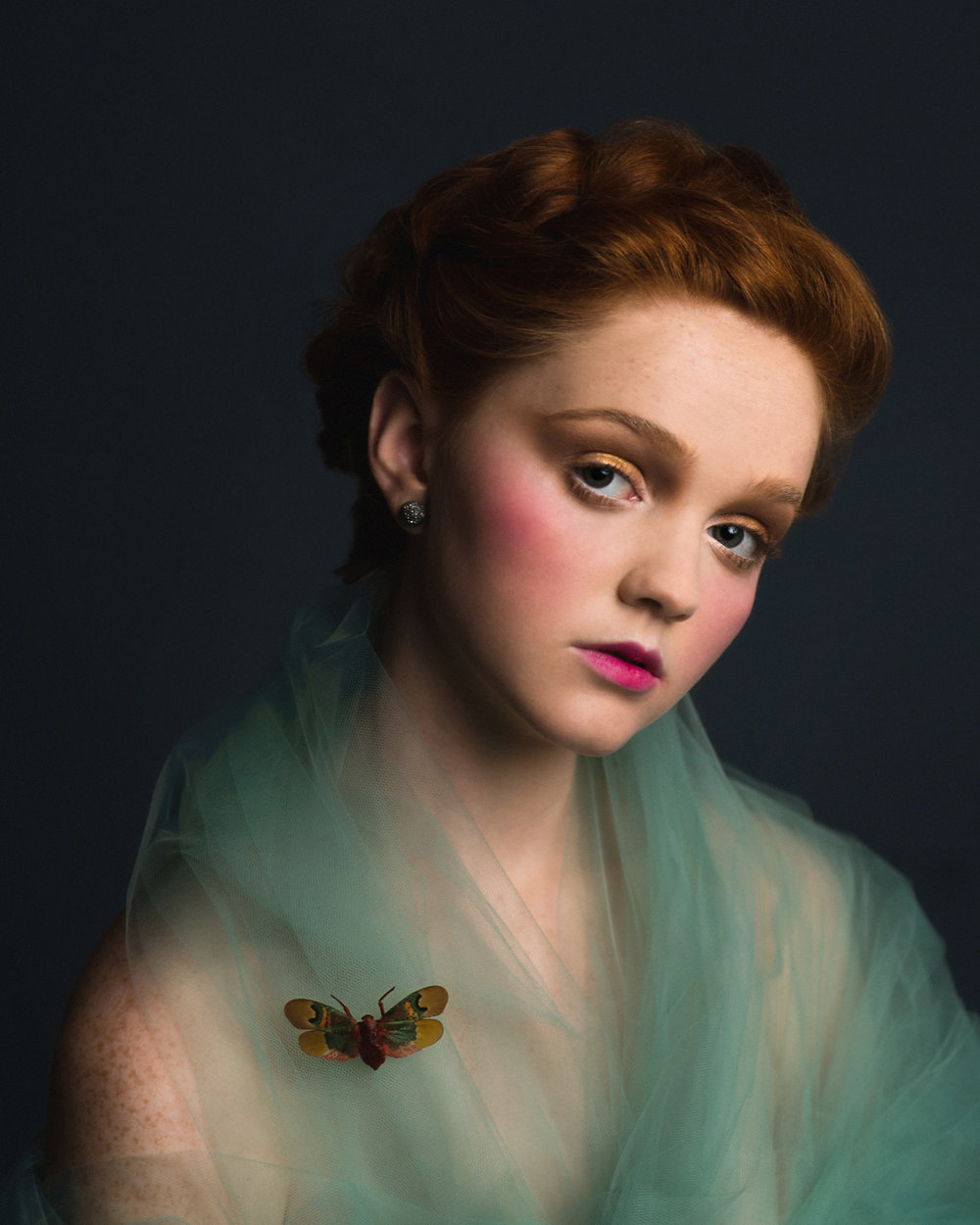 Romantic Victorian inspired studio portrait of a redhead model in tulle with a bright moth. By Sarah Hooker Photography