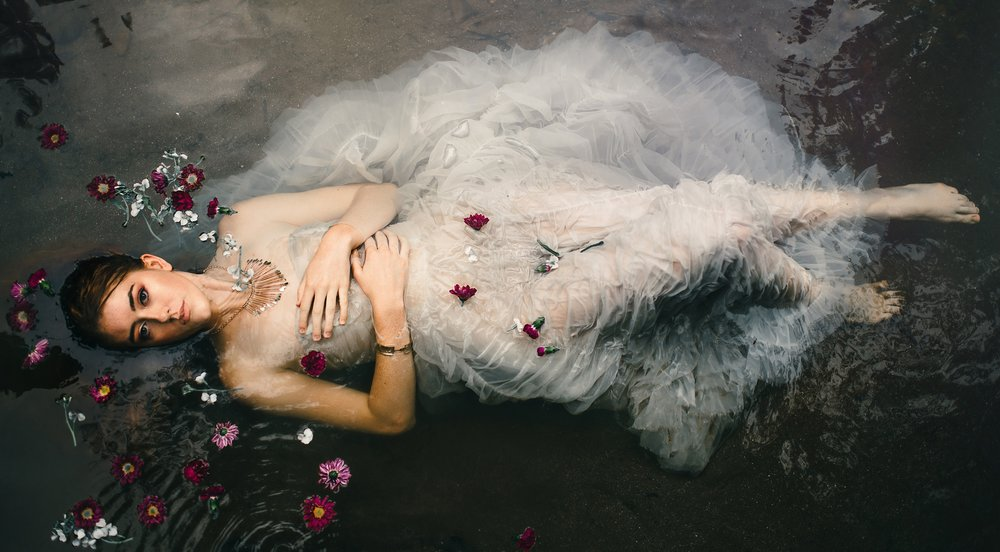 Portrait in the water with flowers and a white vintage dress by Sarah Hooker Photography