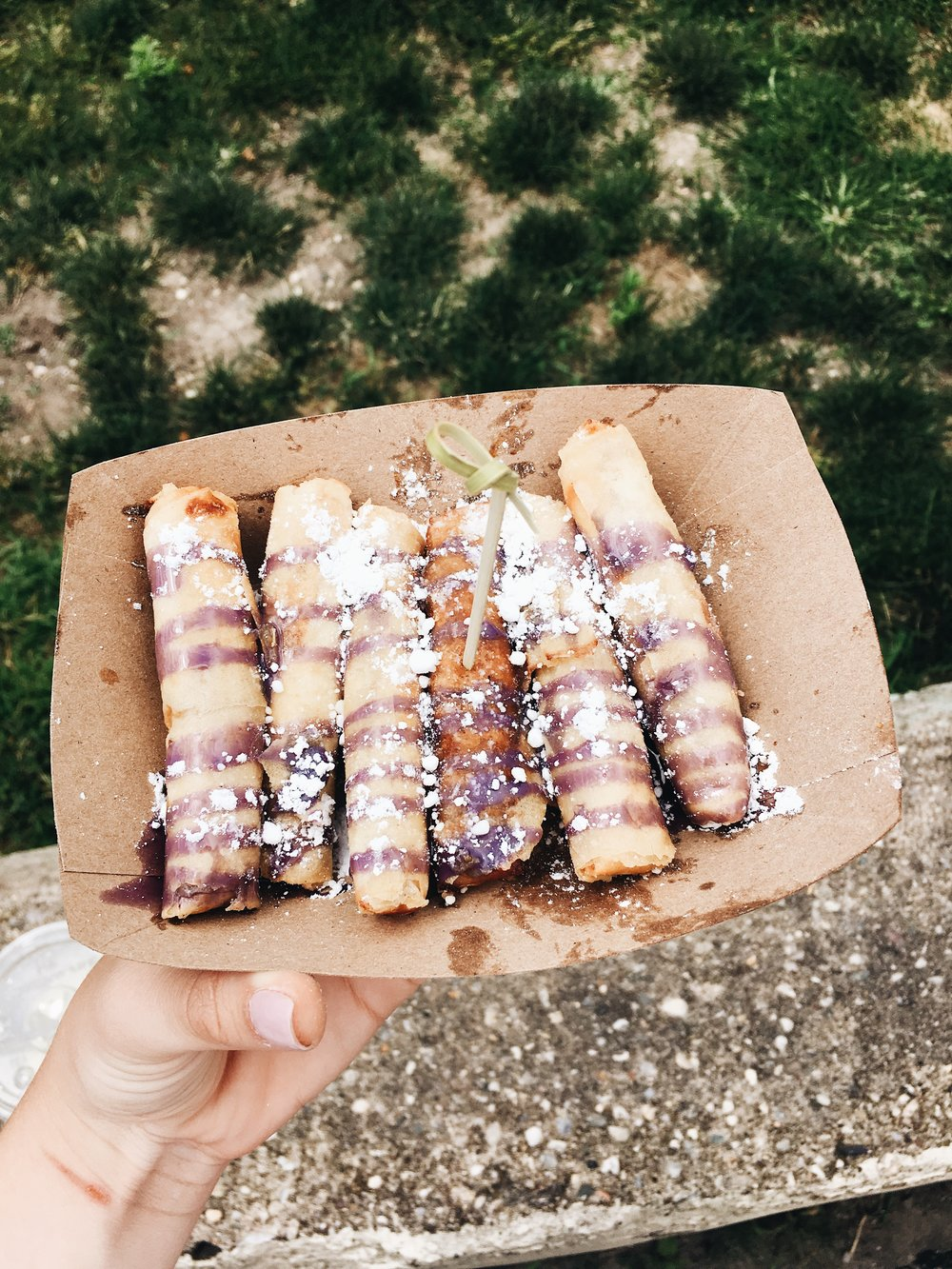 turon- a filipino fried spring roll filled with sweet plantains topped with ube drizzle and powdered sugar