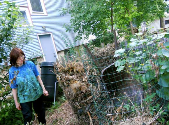 Estelle Carol at the composting pile in her yard. (Photo by Cassandra West)