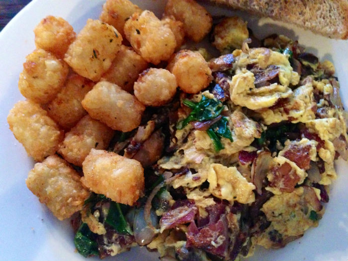 Tater tots and eggs scrambled with spinach, mushrooms, bacon and shallots