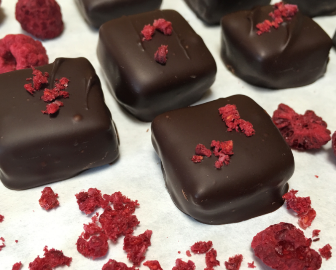 Scrumptiously delicious raspberry ganache truffles. Top them with freeze dried raspberry crumbles for an extra festive note