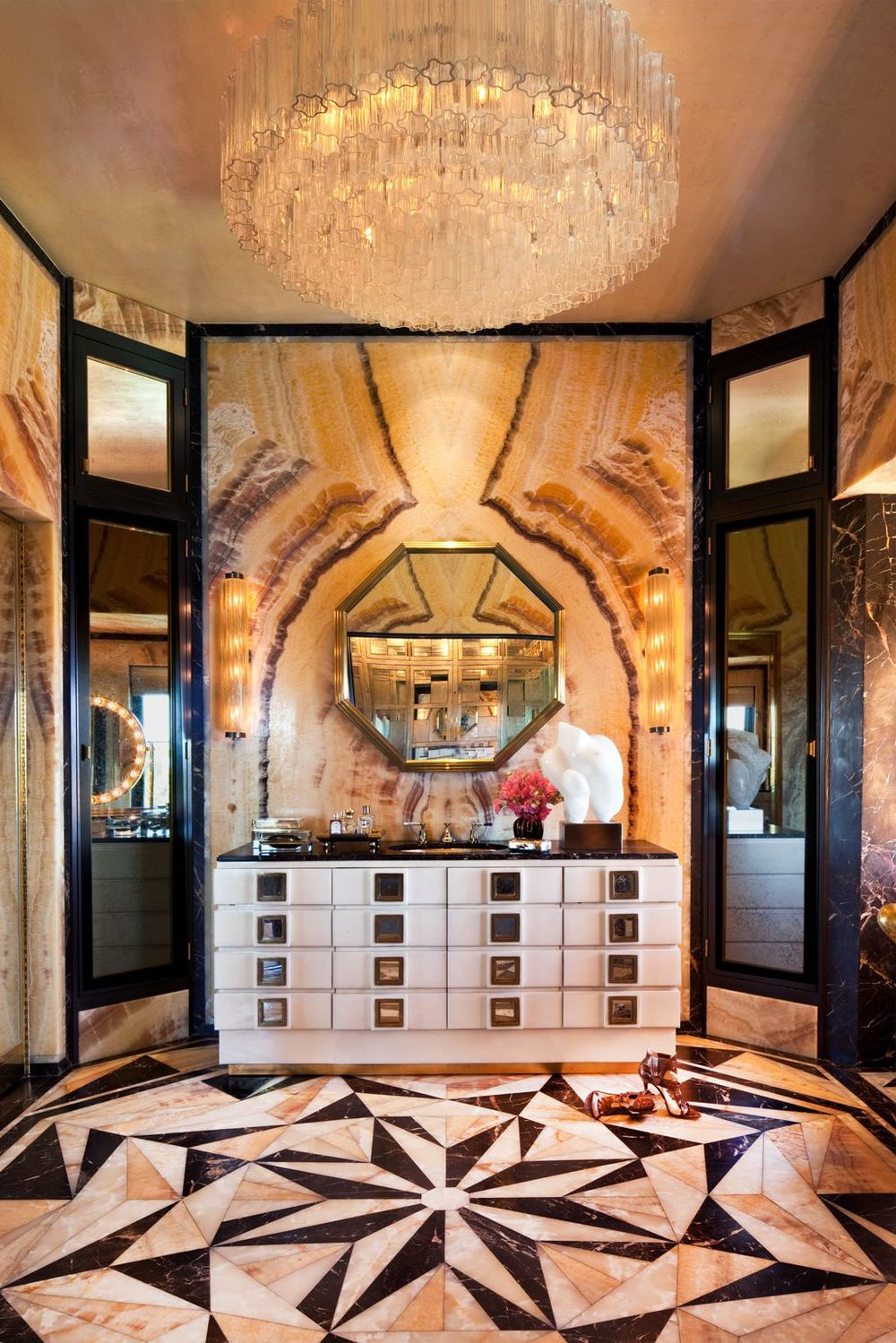 Book–matched onyx coexists with a variety of graphic marbles in this serenely timeless lady's grand bathroom.
