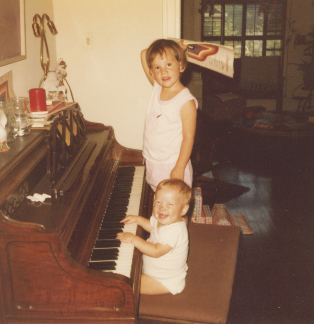My sister Solana and me at the piano. She looks more serious and I am just cracking up.