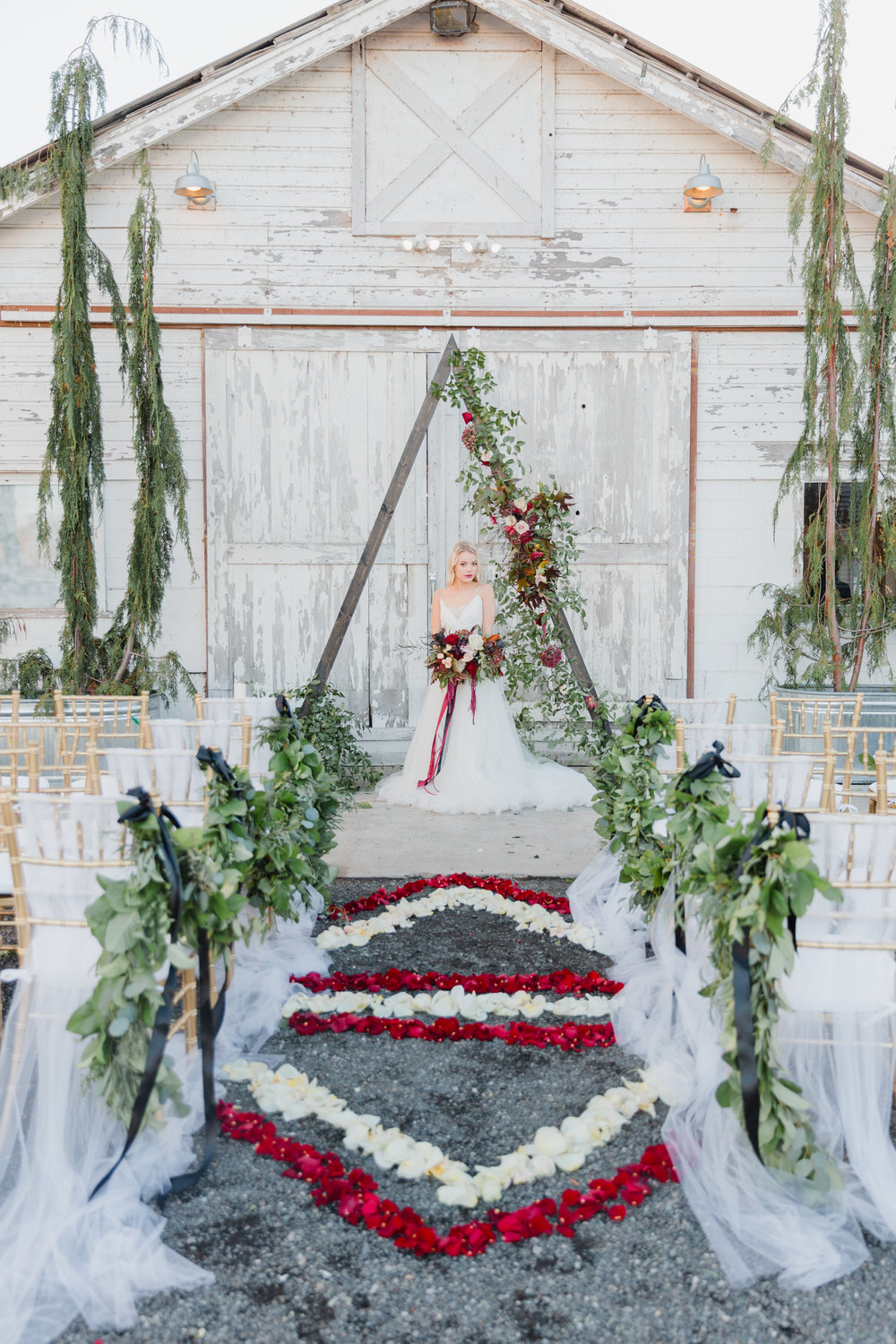 Modern geometric aisle decor with rose petals, garland, and triangle arch by From the Ground Up Floral.