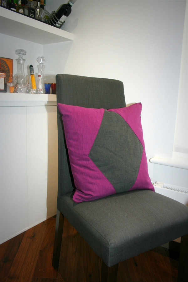 Upholstered purple cushion with a grey, diamond-shaped panel in the centre on a chair that is upholstered in matching grey fabric