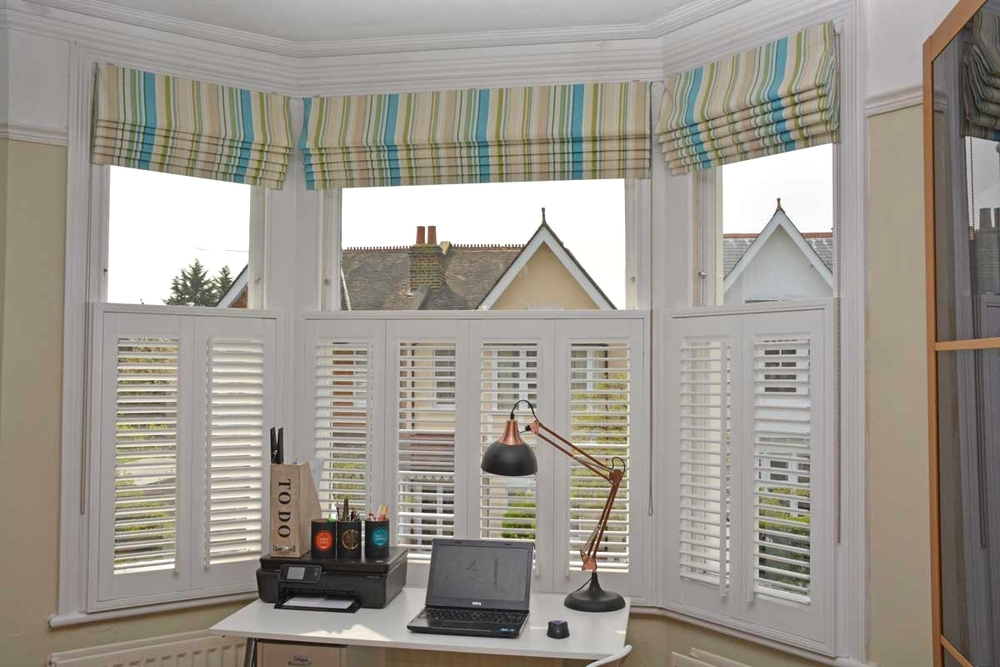 Roman blind with vertical striped fabric in a teal colour palette