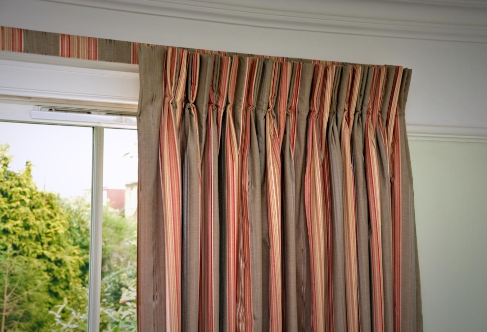 Orange and brown vertically striped curtains with matching, covered lath