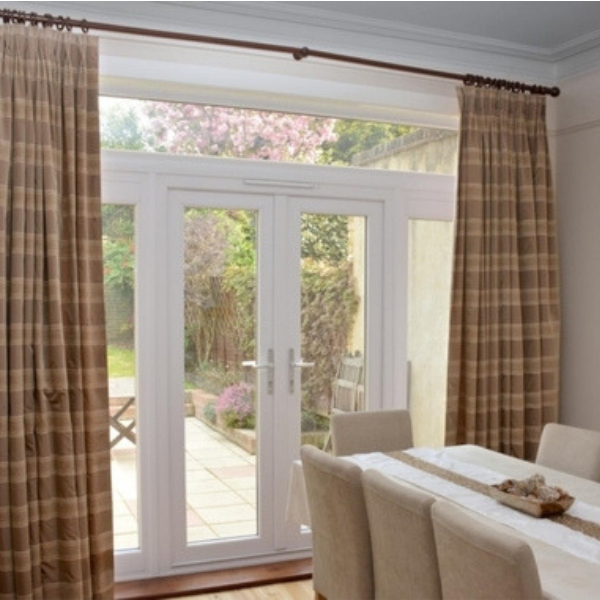 Bespoke, full-length brown and cream fabric curtains, with double pleat heading, framing glass double doors to a spring garden.