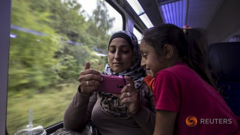 A Syrian Migrant mother and daughter on the train to Austria, looking at their smartphone, the most important tool in making the migration from Syria to Europe.
