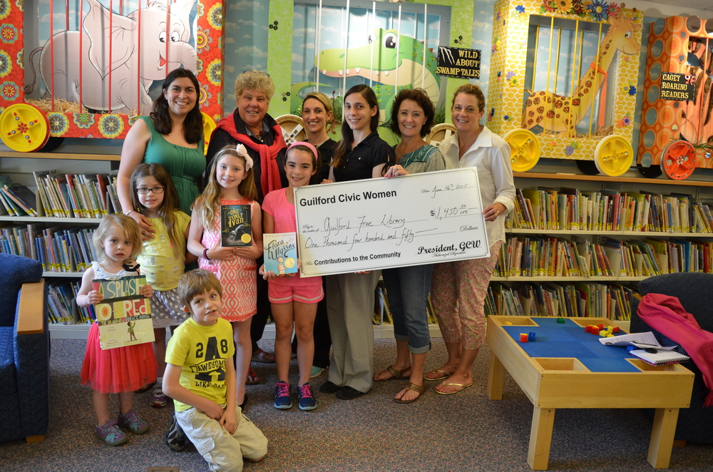 For 25 years, GCW has happily funded the Guilford Free Library's summer reading program, which is open to children and teens. Here GCW members Amanda Waggoner, Courtney Trotta, Joann Nault, and Lee Beatty present a check to director Sandy Ruoff and children's librarian Angelina Carnevale. also pictured are patrons Jack, Ivy, and Claire Waggoner, Alexis Vieau, and Annabel Beatty.