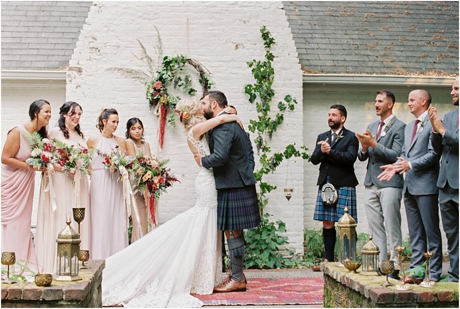 Bohemian bride and scottish groom kiss at their Leach Botanical Garden wedding ceremony.