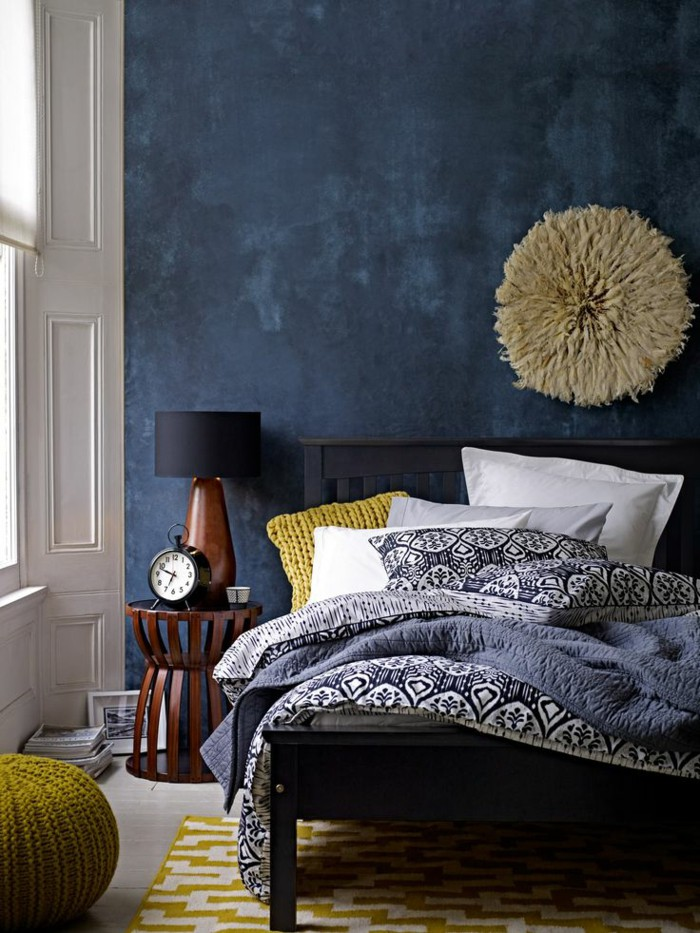 The white walls and mustard rug balance the blue wall nicely.