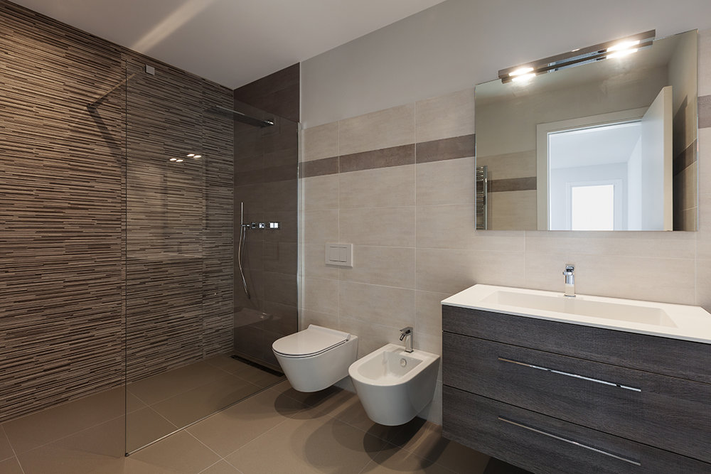 Walk-in shower with single glass panel, wall-hung toilet and bidet. Floating vanity and mirror.