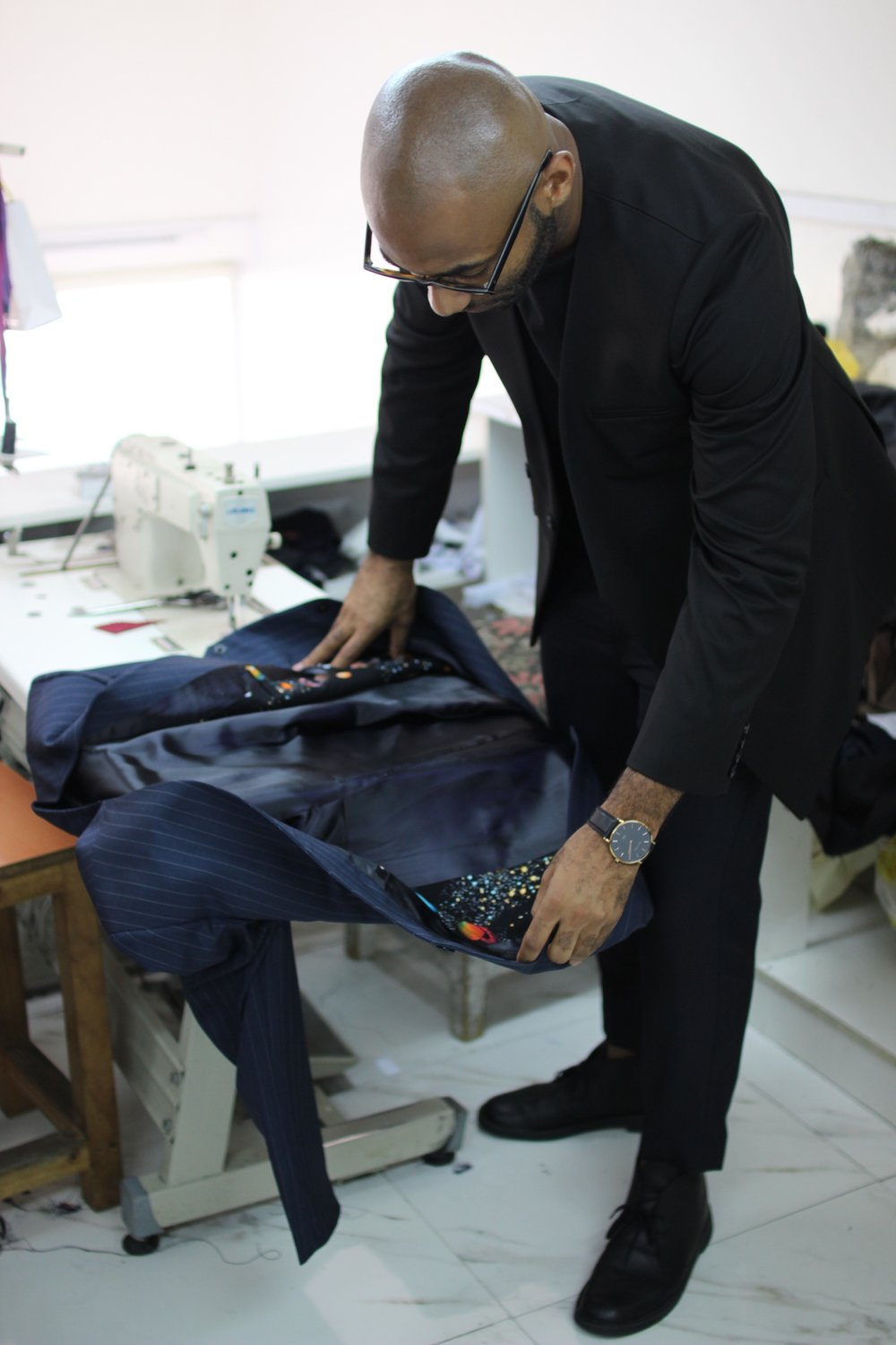 Anthony Caton in studio, viewing the celestial pattern of a jacket lining