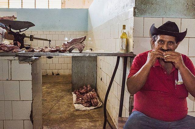 A butcher in a small local market of Santiago de Cuba, enjoying a healthy bite of his pork sandwich.