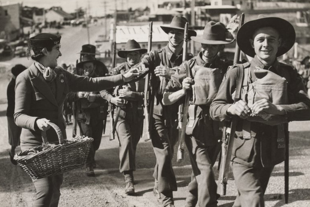 Soldiers during a march to Bathurst. ca. 1940 (World War II) The photograph shows women from Wentworth Falls handing sprigs of wattle to soldiers as they pass. Image courtesy of Argus Newspaper Collection of Photographs, State Library of Victoria.