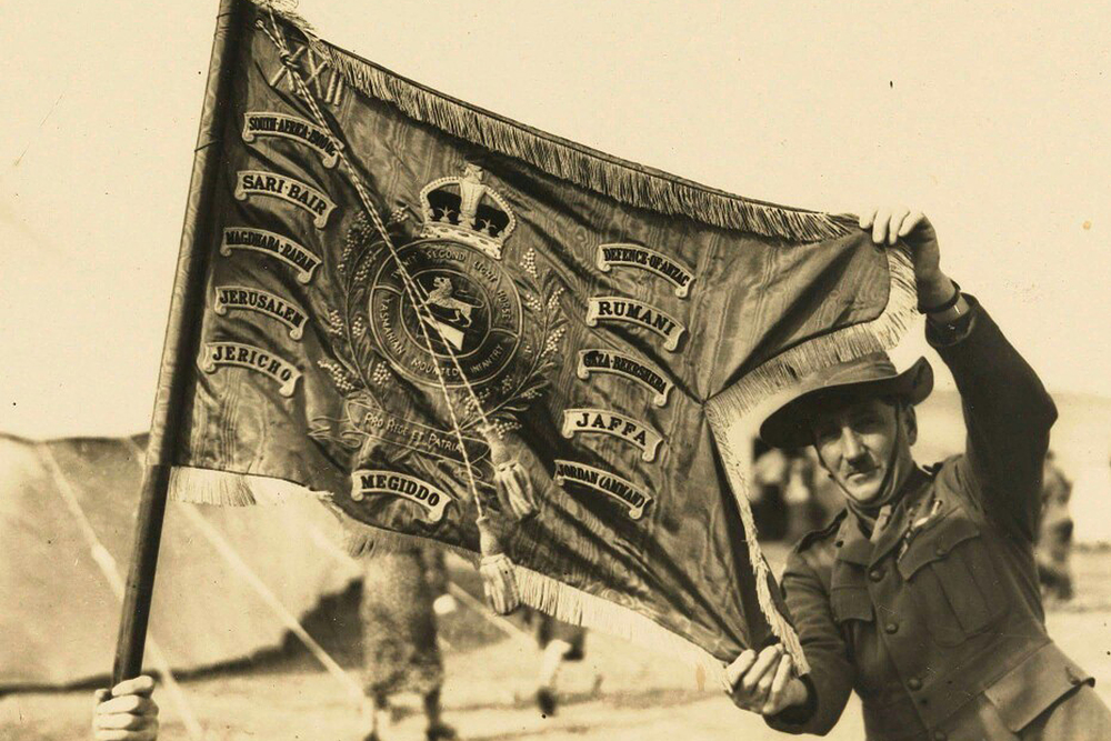 An Australian soldier holding the guidon of the Tasmanian Lighthorse. The central emblem includes two sprigs of wattle.