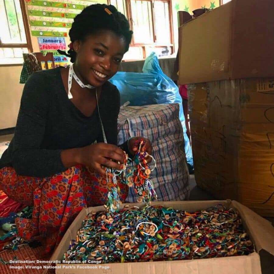 A PARTICIPANT IN THE SEWING COOPERATIVE FORN FALLEN RANGER'S FAMILIES SMILES AS SHE HELPS PACK UP AN ESPECIALLY LARGE COMPLETED ORDER OF BRACELETS. IMAGE: VIRUNGA NATIONAL PARK FACEBOOK PAGE