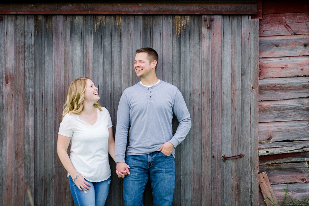 Outdoor, country styled engagement session near Audubon, MN | laughing in front of old barnwood | Amer Langerud Photography